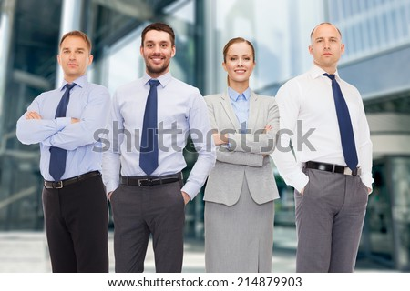 business, partnership and people concept - group of smiling businessmen over business center background - stock photo