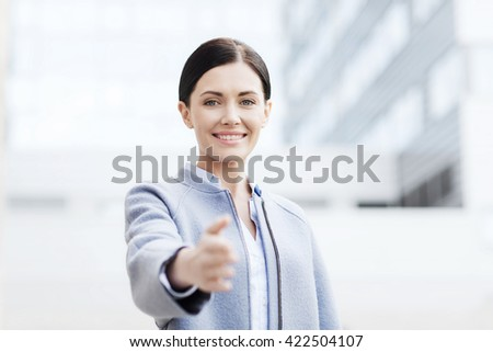 business, partnership, cooperation and people concept - young smiling businesswoman giving hand for handshake over office building - stock photo