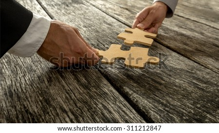 Business partnership or teamwork concept with a business people presenting a matching puzzle piece as they cooperate on finding an answer and solution, close up of their hands. - stock photo