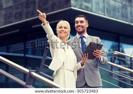 business, partnership, technology and people concept - smiling businessman and businesswoman with tablet pc computer over office building - stock photo