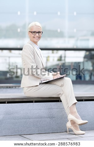 business, people and education concept - young smiling businesswoman in glasses with notepad over office building - stock photo