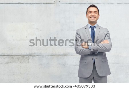 business, people and office concept - happy smiling businessman in suit over gray concrete wall background - stock photo