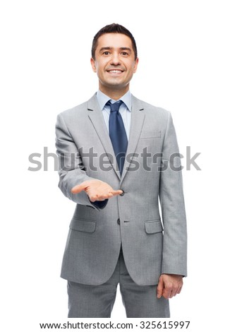 business, people and office concept - happy smiling businessman in suit showing something imaginary on empty palm - stock photo