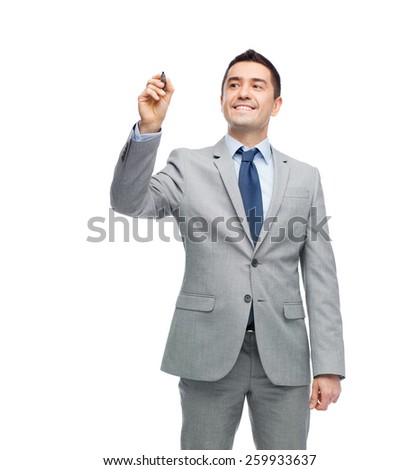 business, people and office concept - happy smiling businessman in suit writing or drawing something imaginary with marker - stock photo