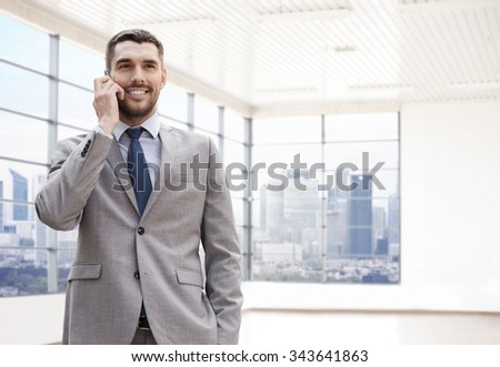 business, people and office concept - happy young businessman calling on smartphone over office room or new apartment background - stock photo