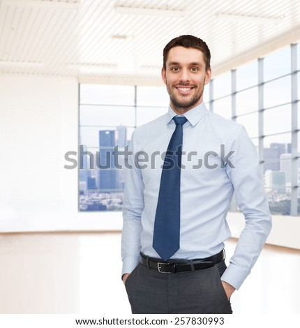 business, people and office concept - happy young businessman over office room or new apartment background - stock photo