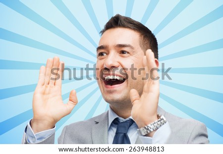 business, people and public announcement concept - happy businessman in suit shouting over blue burst rays background - stock photo