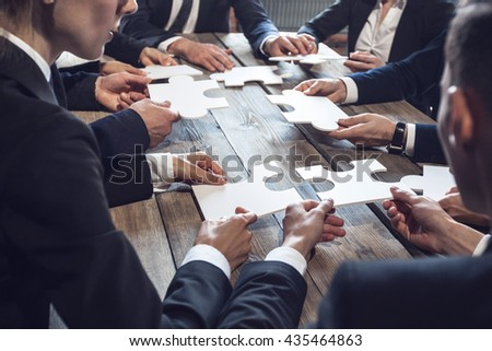 Business people and puzzle on wooden table, teamwork concept - stock photo
