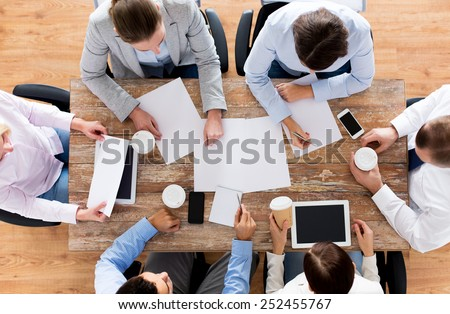 business, people and team work concept - close up of creative team with papers and gadgets meeting and drinking coffee in office - stock photo