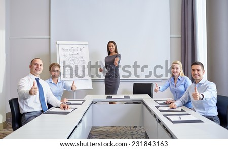 business, people and teamwork concept - group of smiling businesspeople meeting and showing thumbs up in office - stock photo