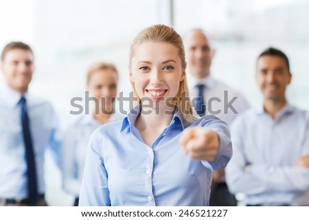 business, people and teamwork concept - smiling businesswoman pointing finger on you with group of businesspeople in office - stock photo