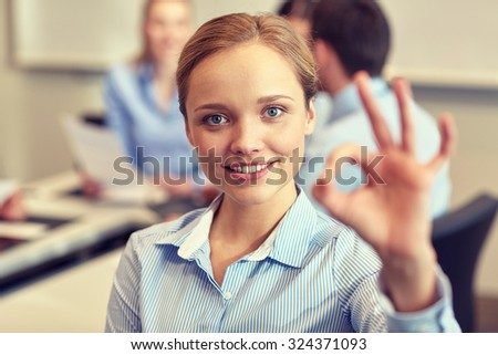 business, people and teamwork concept - smiling businesswoman showing ok gesture with group of businesspeople meeting in office - stock photo
