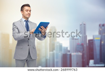 business, people and technology concept - happy businessman in suit holding tablet pc computer over city background - stock photo