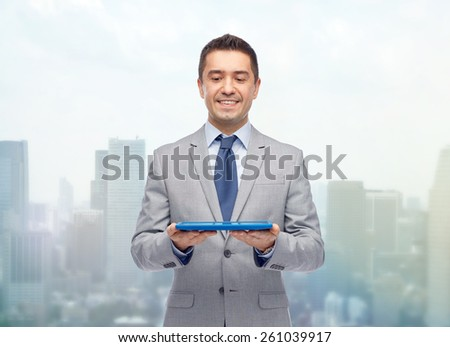 business, people and technology concept - happy smiling businessman in suit holding tablet pc computer over city background - stock photo