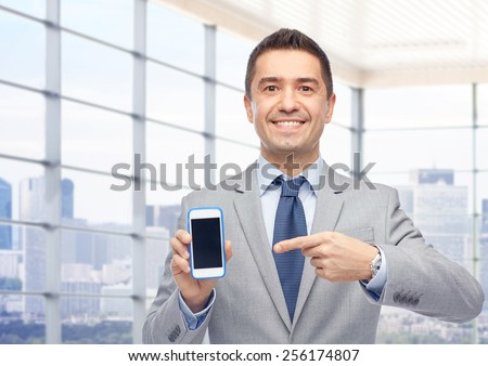 business, people and technology concept - happy smiling businessman in suit showing smartphone black blank screen over city office window background - stock photo