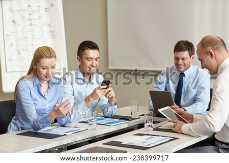 business, people and technology concept - smiling business team with smartphone and papers meeting in office - stock photo