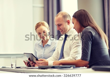 business, people and technology concept - smiling business team with tablet pc computer meeting in office - stock photo
