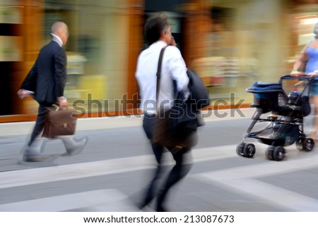 Business people and woman with stroller in the street. Intentional motion blur - stock photo