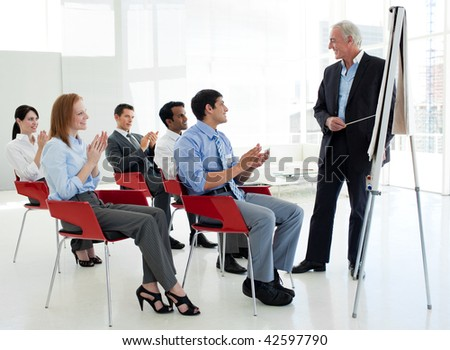 Business people applauding at the end of a conference in the office - stock photo
