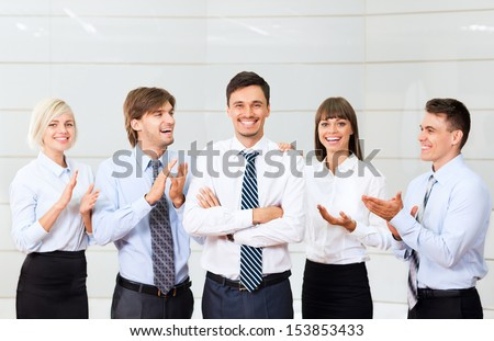 Business people applauding congratulating colleague, boss, team leader success, businesspeople group smile, at modern office - stock photo