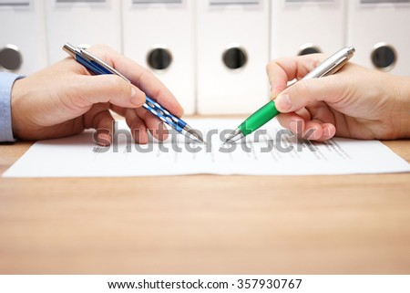 business people are examining document on table - stock photo