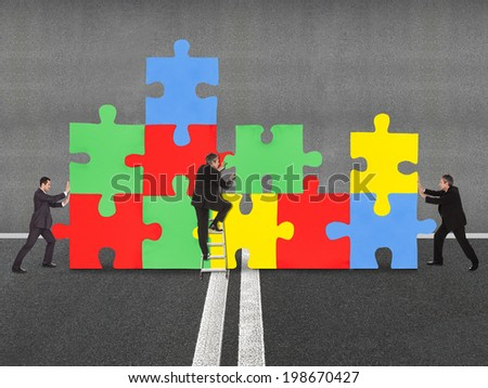 Business people assembling jigsaw puzzle representing teamwork - stock photo