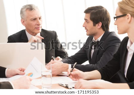 Business people at the meeting. Four business people in formalwear communicating while sitting together at the meeting - stock photo