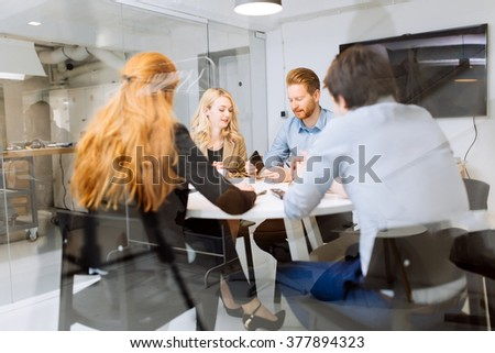 Business people board meeting in modern office while sitting at round table - stock photo