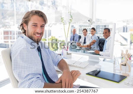 Business people brainstorming against smiling designer sitting at his desk - stock photo