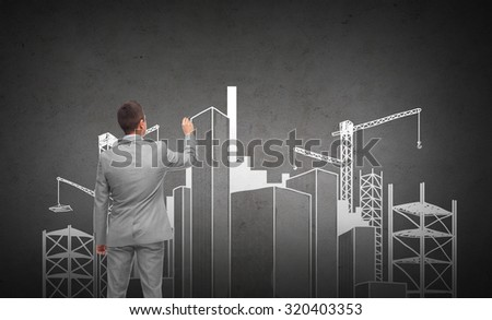 business, people, building, city and planning concept - businessman drawing construction site sketch from back over dark gray concrete wall background - stock photo