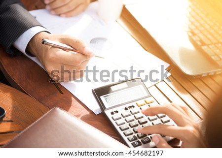 Business people calculating and discussing financial documents with calculator and laptop computer on the table - stock photo
