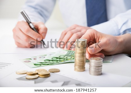 Business people calculating profit - closeup shot of hands counting banknotes and coins and making notes on paper - stock photo