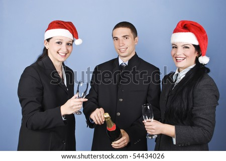 Business people celebrating Christmas with champagne and having fun,wearing Santa hats and laughing together - stock photo