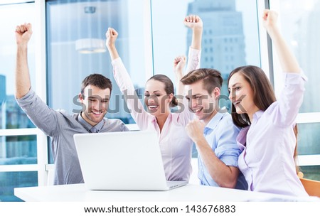 Business people cheering at laptop - stock photo