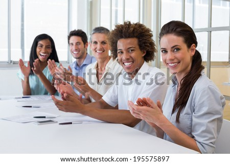 Business people clapping and smiling at camera in the office - stock photo