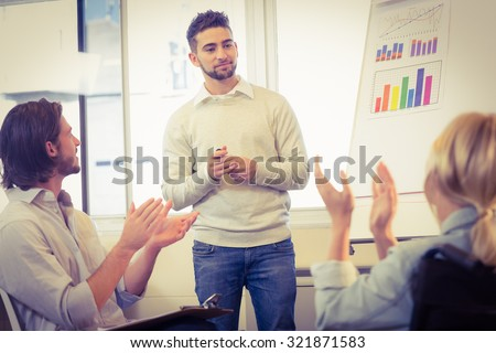 Business people clapping for confident male colleague for his successful presentation in creative office - stock photo