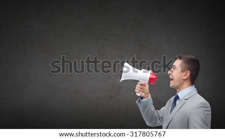 business, people, communication and public announcement concept - happy businessman in suit speaking to megaphone over dark gray concrete wall background - stock photo