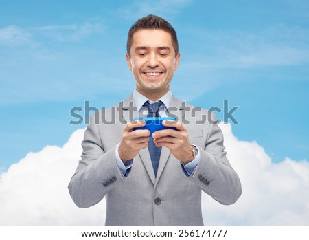 business, people, computing, network and technology concept -happy businessman texting or playing game on smartphone over blue sky and cloud background - stock photo