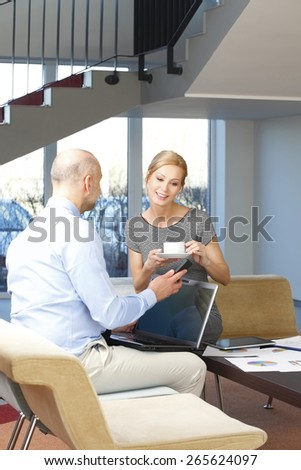 Business people consulting while sitting at office and business woman drinking coffee. - stock photo