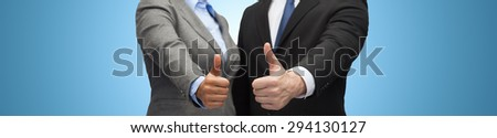 business, people, cooperation, success and gesture concept - businessman and businesswoman showing thumbs up over blue background - stock photo