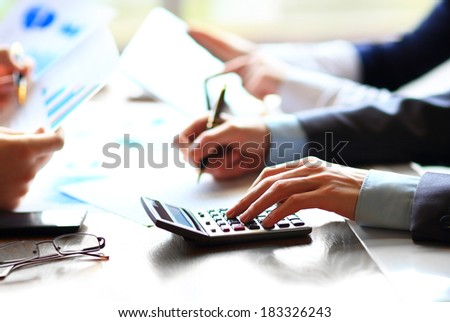 Business people counting on calculator sitting at the table. Close up of hands and stationery - stock photo