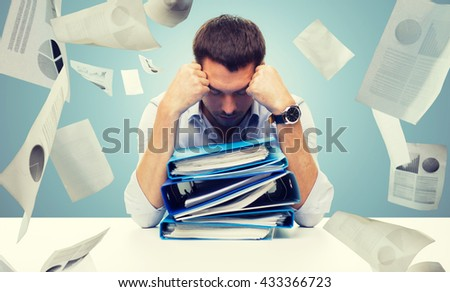 business, people, deadline, stress and paperwork concept - sad businessman with stack of folders and falling papers over blue background - stock photo