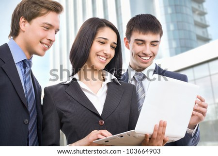 Business people discuss a new project outside modern office building - stock photo