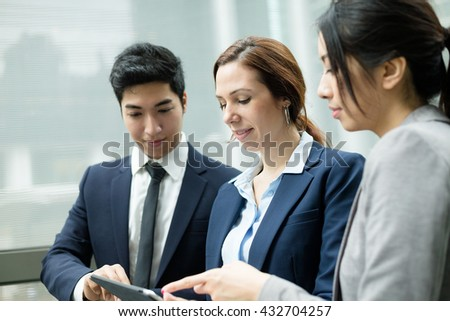 Business people discuss on tablet computer - stock photo