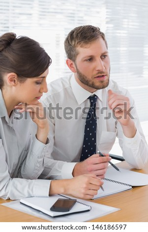 Business people discussing documents at desk in office - stock photo