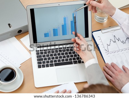 Business people discussing graphs on the laptop sitting at the table. Close up of hands and laptop - stock photo