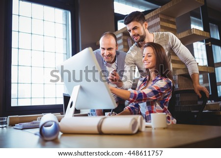 Business people discussing over computer at desk in creative office - stock photo