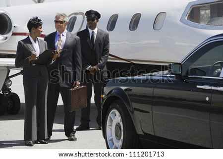 Business people discussing reports with driver in the background at airfield - stock photo