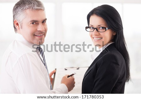 Business people doing paperwork. Two smiling business people writing something in note pad and looking over shoulder - stock photo