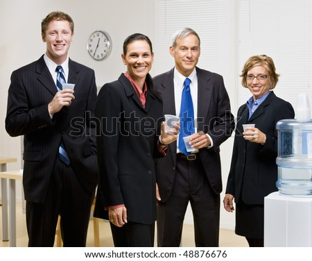 Business people drinking water at water cooler - stock photo